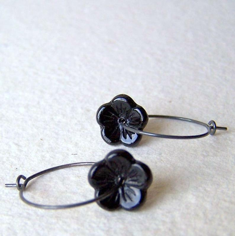 Vintage black glass flower beads are threaded onto oxidized sterling silver hoop earrings.