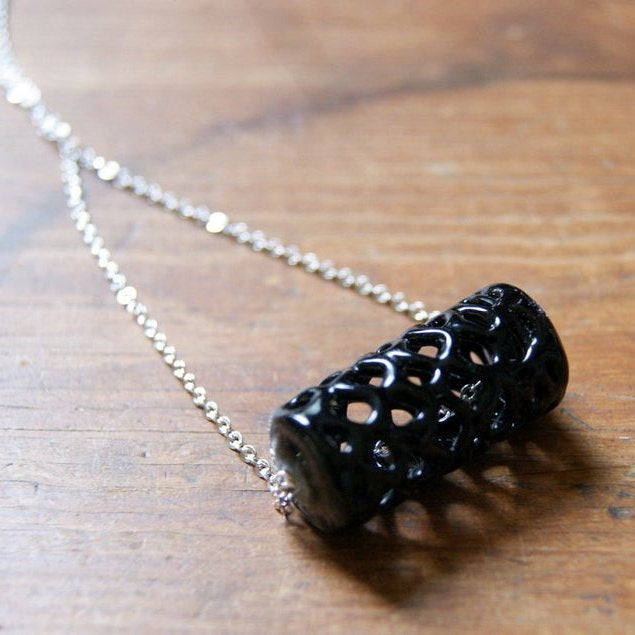 Necklace made by threading a vintage black lace glass bead onto a vintage silver plated chain.