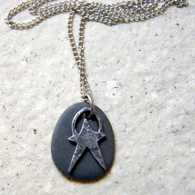 A black beach stone with a pewter star charm necklace.
