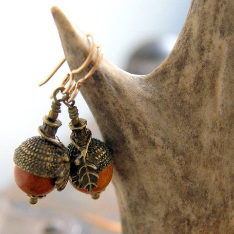 Acorn earrings made by combining redwood beads and antiqued brass acorn bead caps. They hang from gold filled french earwires by Wear Your Wild.