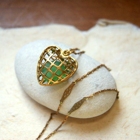 Necklace made with a vintage brass cage heart locket filled with green sea glass.