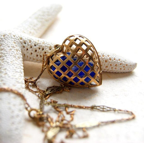 A necklace made with a vintage brass cage style heart locket filled with sea glass, hanging from a vintage brass chain.