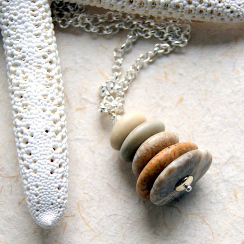 A Cairn necklace made by stacking five smooth beach stones.