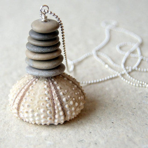 A Cairn necklace made with seven beach stones hung from a ball chain by Wear Your Wild.