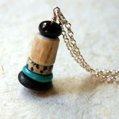 A Cairn necklace made with a combination of jet, deer antler bead, dalmation jasper, turquoise and black river rock.