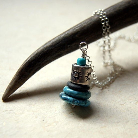 A Cairn necklace made with turquoise, a black river stone and a Hill Tribe silver sun bead.