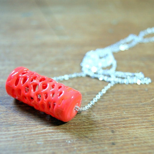 A vintage coral colored lace glass tube bead is threaded onto a vintage silver plated chain to make this necklace.