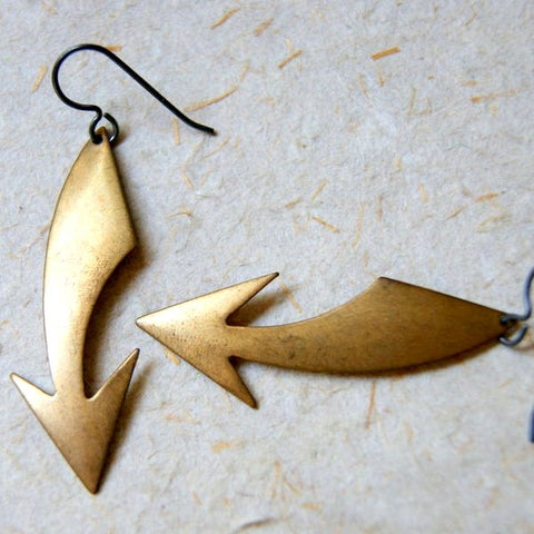 Curved brass arrow earrings that have been slightly oxidized for an industrial look.