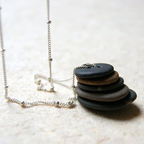 Cairn necklace made by stacking five double drilled beach stones on a sterling silver satellite chain.