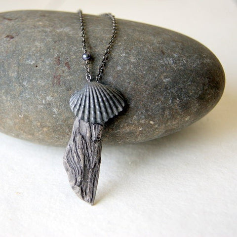 A gray stoneware driftwood pendant is paired with a vintage charcoal gray metal shell and hung from a gunmetal chain. The chain is connected together with a black freshwater pearl.