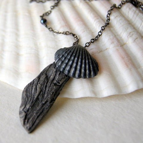 A gray stoneware driftwood pendant is paired with a vintage charcoal gray metal shell and hung from a gunmetal chain. The chain is connected together with a black freshwater pearl by Wear Your Wild