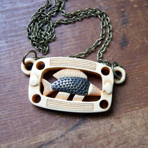Necklace made by suspending a vintage brown and beige Lucite fish pendant from an antiqued brass chain.