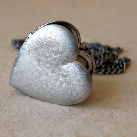 A large vintage silver plated brass heart locket necklace with a vintage stainless steel chain.