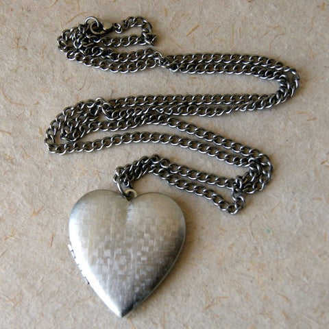 A large vintage silver plated brass heart locket necklace with a vintage stainless steel chain by Wear Your Wild