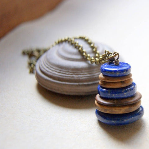 A Cairn necklace made with Lapis Lazuli and coconut shell discs hanging from an antiqued brass chain by Wear Your Wild