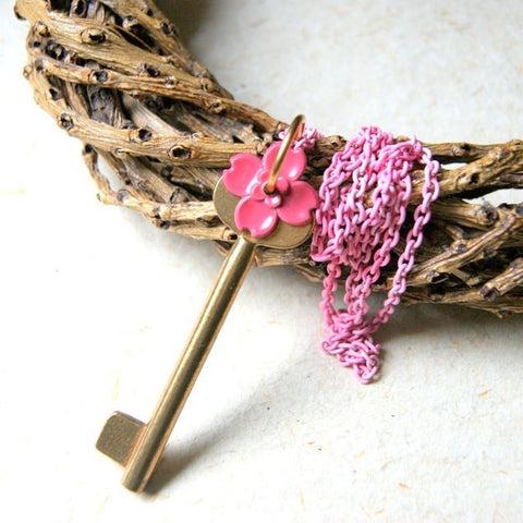 Necklace made by combining a vintage brass key with a vintage pink enameled flower. They are hung on a vintage pink enameled chain.