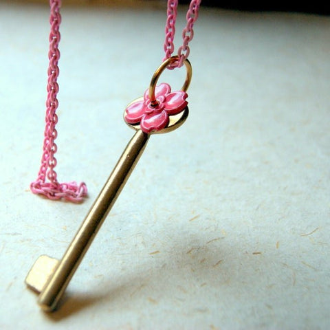 Necklace made by combining a vintage brass key with a vintage pink enameled flower. They are hung on a vintage pink enameled chain by Wear Your Wild