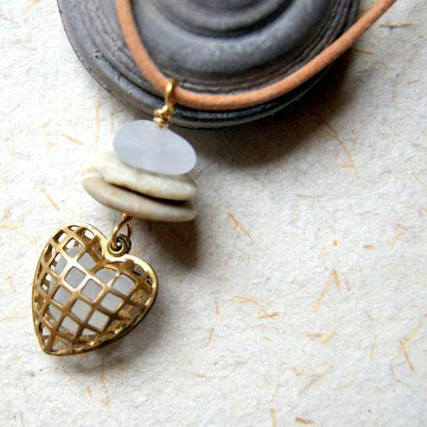 A petite beach stone Cairn necklace with four stones in shades of beige and tan hanging from a sterling silver chain by Wear Your Wild