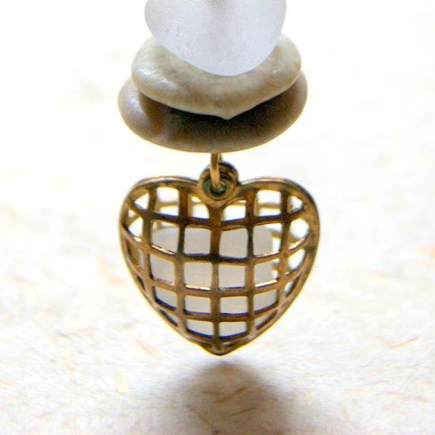 A necklace made by combining a vintage brass cage heart locket filled with white sea glass and a cairn comprised of beach stones and sea glass.