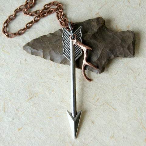 Necklace made by combining a silver arrow pendant and a copper antler charm that hang from an antiqued copper chain.