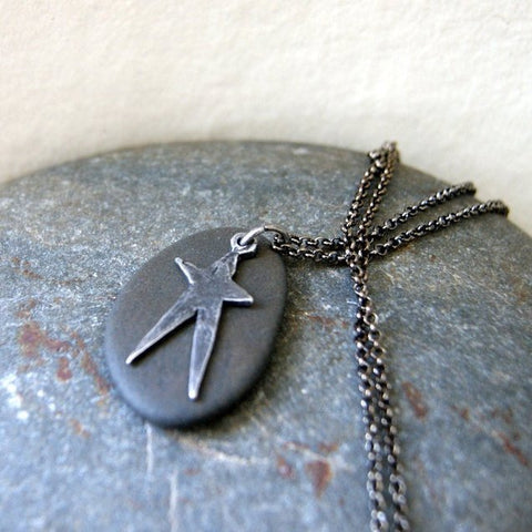 A black beach stone necklace with a pewter star and gunmetal rolo chain.