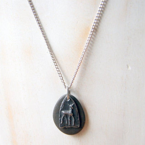 A black beach stone necklace combined with a pewter deer charm. The pendant hangs from a stainless steel chain by Wear Your Wild