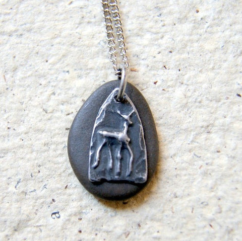 A black beach stone necklace combined with a pewter deer charm. The pendant hangs from a stainless steel chain.