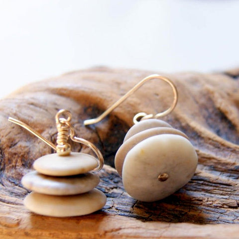 Cairn earrings made by stacking three sandy colored beach stones with gold filled metal.