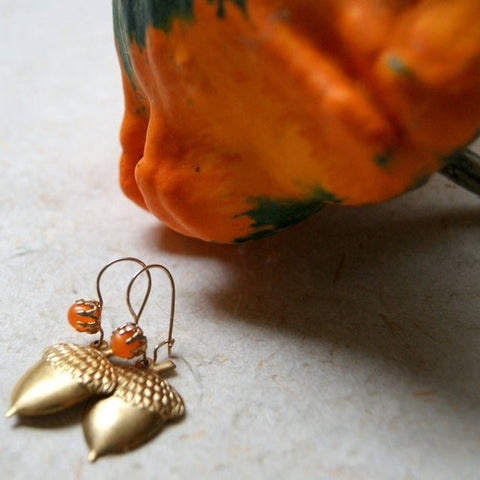 Earrings made with vintage brass acorns hang from vintage brass kidney earwires that are adorned with orange Lucite beads by Wear Your Wild