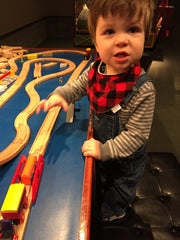 toddler boy in bandana bib playing with toy trains
