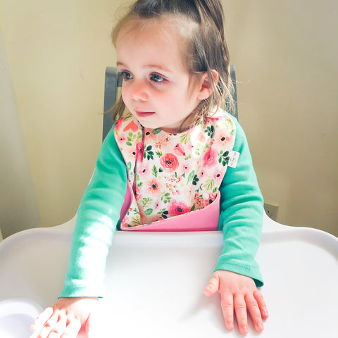 Toddler girl sitting in high chair wearing the Ultimate Meal Bib, a waterproof pocket bib by Milk & Sugar