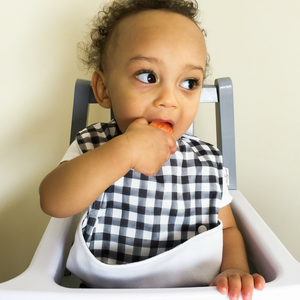 toddler boy eating and wearing the Ultimate Meal Bib from Milk & Sugar Baby, waterproof pocket bib