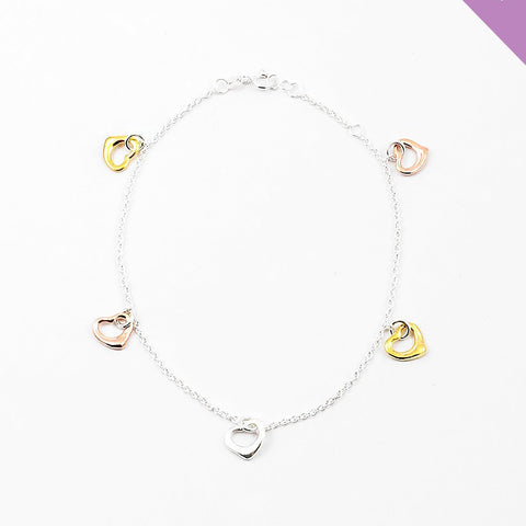 Silver Anklet with gold, rose gold and silver heart carms dangling from anklet.
