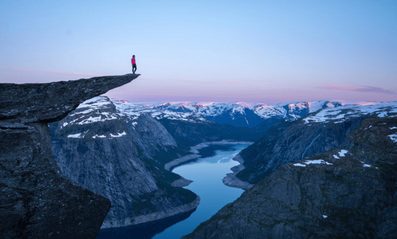 Man standing on the edge of a cliff overlooking a river in adventurous photograph