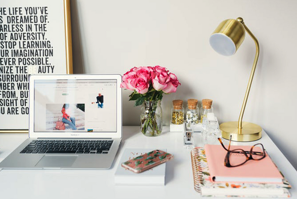 Blog writing fashion blogger desk space with flowers laptop and journal