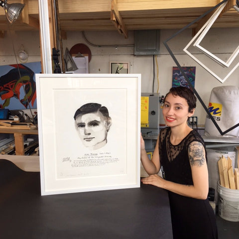 A Frames and Stretcher employee holding Marlene Dumas' portrait of Alan Turing that was floated using Japanese paper and wheat paste and custom framed at Frames and Stretchers on the Lower East Side.