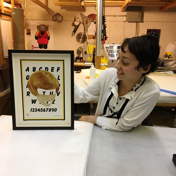 Yvette holding a finished Eva Lake portrait custom framed and floated at Frames and Stretchers in the Lower East Side.