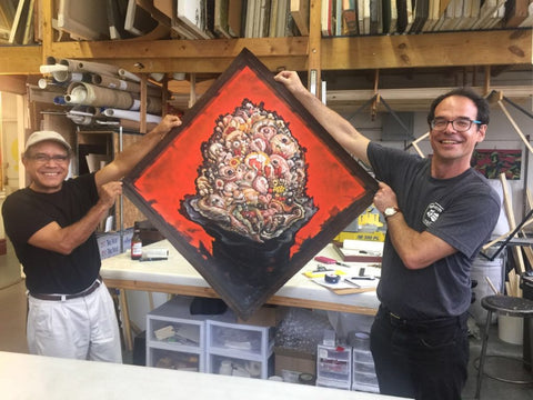 Jose Garcia Cordero and Frames and Stretcher co-founder Miguel Trelles holding up a finished piece.