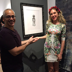 Erick and Monique Mantell in front of the drawings framed by Frames and Stretchers
