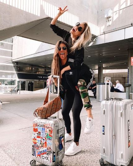 two girls posing at airport beside their suitcases