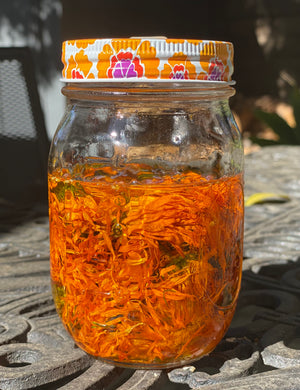 jar of jojoba oil and calendula petals