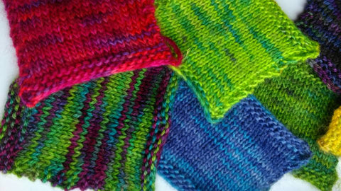 Knitted squares of hand dyed yarns in bright colours