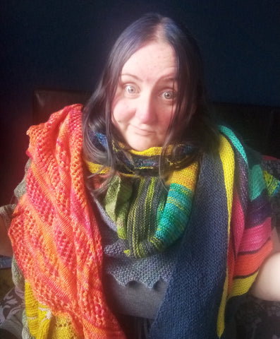 Becky - Ovis Yarns - wearing a pile of hand dyed hand knitted shawls