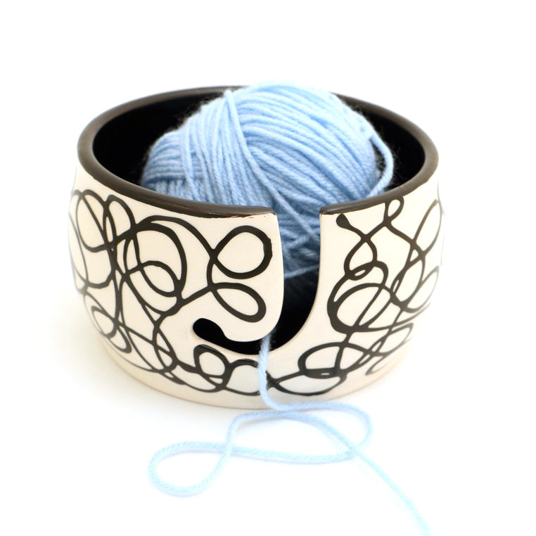 "Handmade ceramic yarn bowl features a pattern called ""tangled"" swirling ellipses of black threads,"