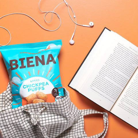 Biena Chickpea Puffs in a bag next to a book