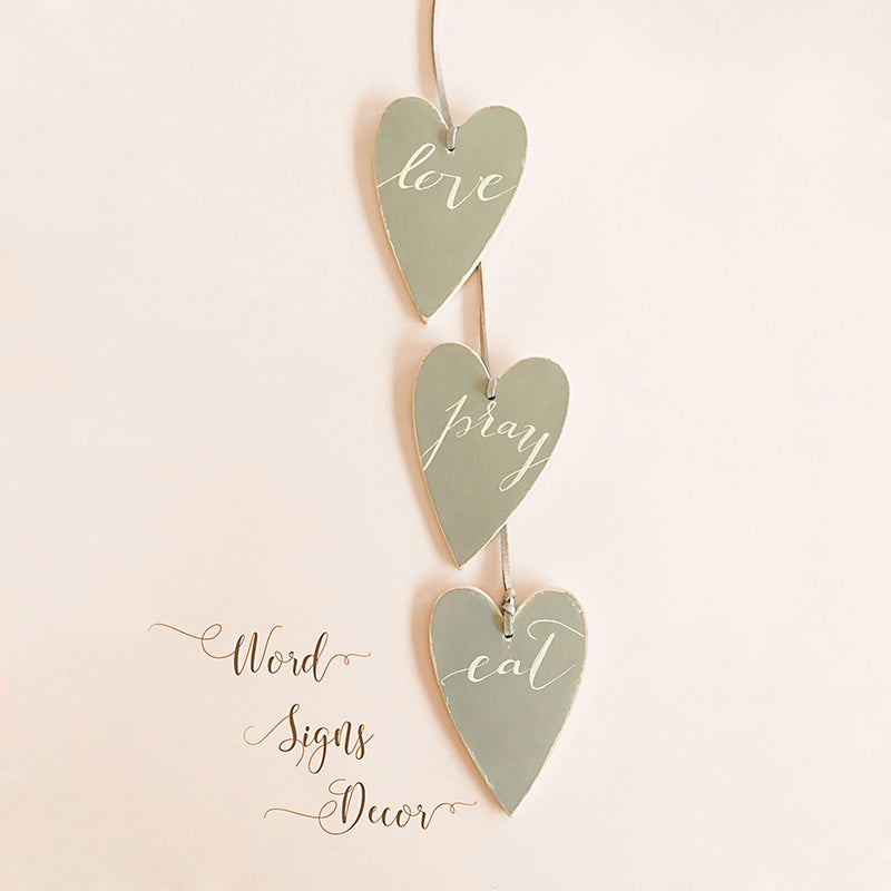 Three hearts painted in grey with white text Eat Pray Love