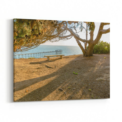 Panoramic Landscape Picture Of A Lonely Wooden Bench With Scenic Ocean View As A BackgroundMonterey, California, United States Canvas Wall Art Print