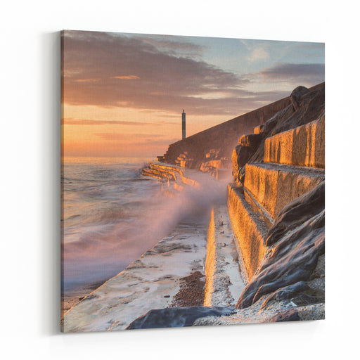 A Wave Rushes Towards The Viewer Along The Pier Wall At Sunset In Aberystwyth, West Wales, UK  The Side Of The Wall Is Lit By The Setting Sun, A Long Exposure Softens The Wave Canvas Wall Art Print