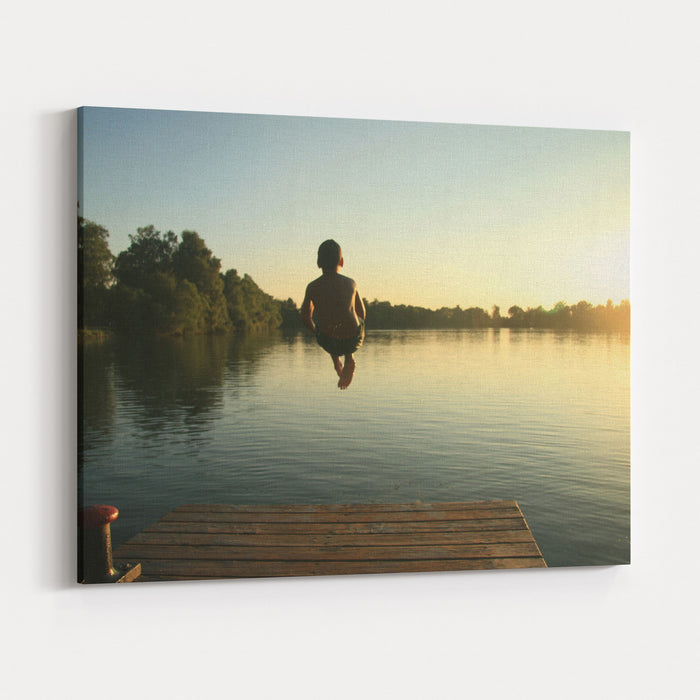 Boy Jumping Into A Lake From A Dock At Sunset In The Summer Canvas Wall Art Print