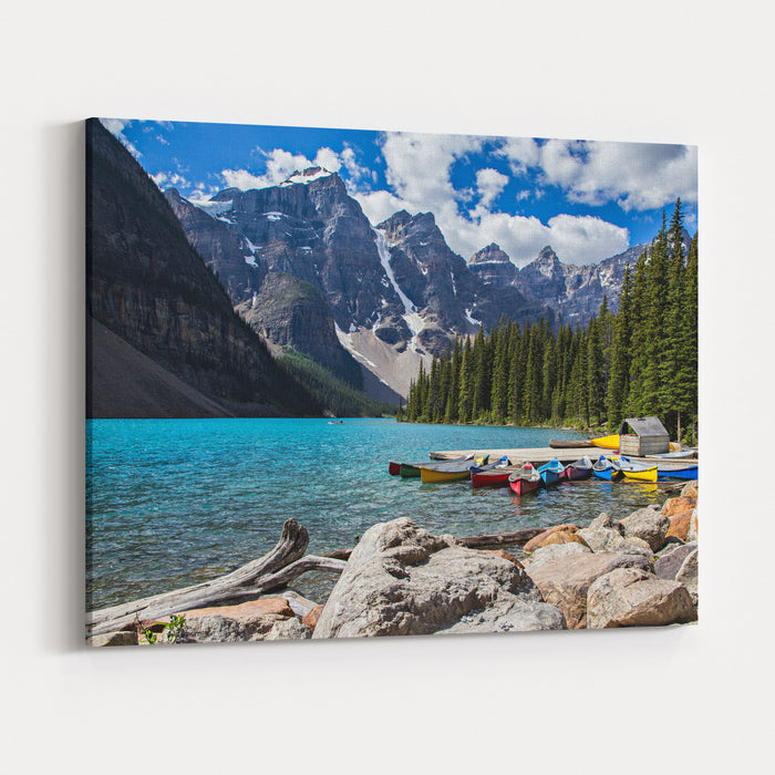 Rocky Mountain View At Moraine Lake In Banff National Park Blue Glacial Water And Fir Trees With Canoes Canvas Wall Art Print